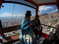 Women ride in a cable car during a media preview of an urban ropeway between El Alto and La Paz