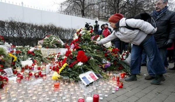 A woman puts flowers near the French embassy to commemorate victims of the Paris attacks, in Moscow, Russia